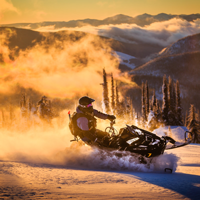 Billy Stevens snowmobiling with the sunset behind him.