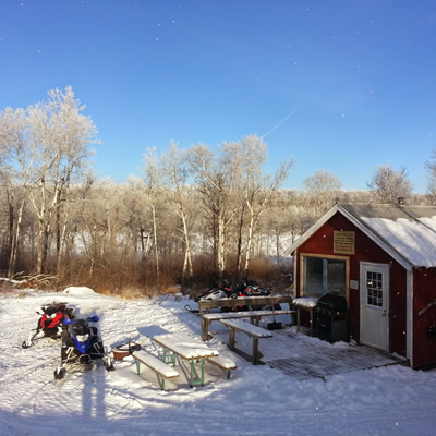 Sleds parked outside a snowmobile cabin near Birch Hills, Saskatchewan.