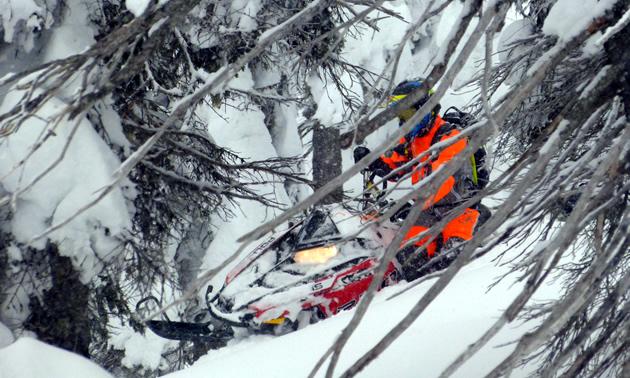 Snowmobiler in an orange Blitzkrieg monosuit from Motorfist.