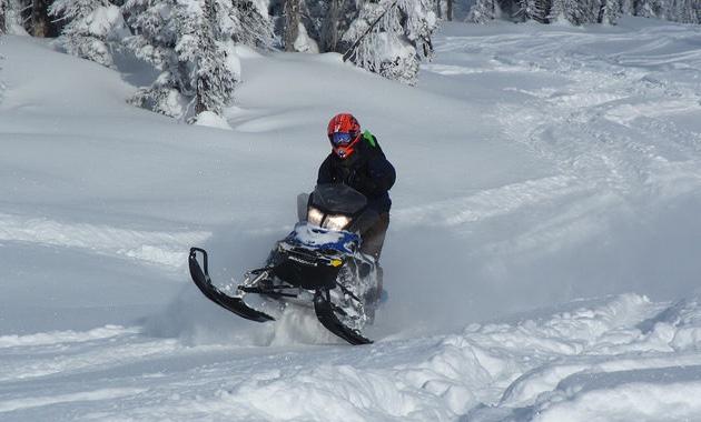 Snowmobiler in a red helmet riding in fresh powder.