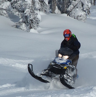 Snowmobiler in a red helmet riding in fresh powder.