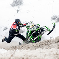 Bent Pukas dangles off his sled in a hillclimb race for RMSHA.