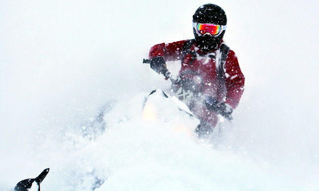 Brianna Lukkar dips her sled into some while gold while snowmobiling around Revelstoke.
