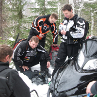 Riders gathered around a broken sled.