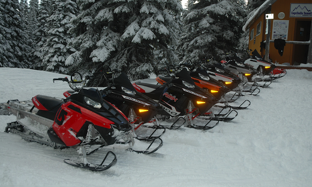 Snowmobiles lined up in front of a cabin.