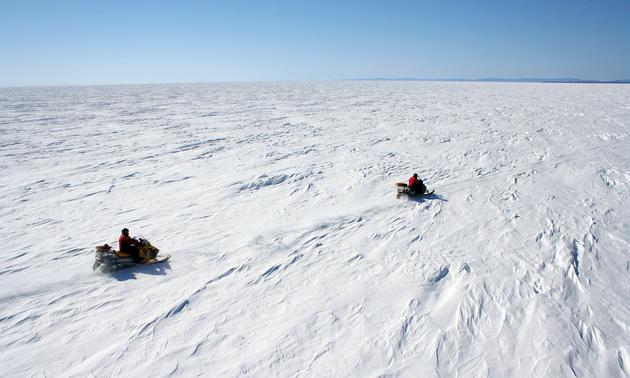 people sledding on a wide open snowy plain
