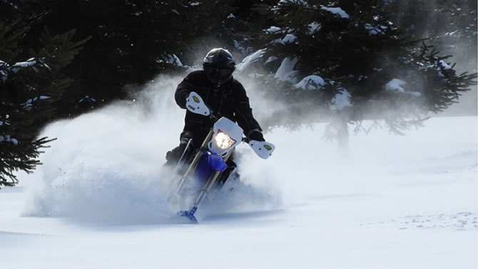 The Camso dirt-to-snow bike conversion system allows riders to switch the front wheel of their off-road motorcycle with a ski and the rear drive systems with a tracked undercarriage.