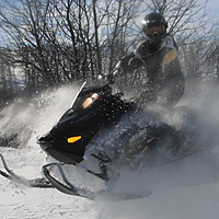A man on a black sled playing in the powder.