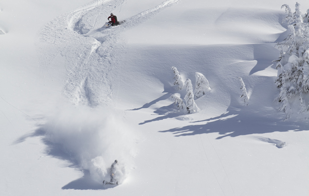 Photo of two snowmobilers riding down a steep mountain with lots of fresh snow.