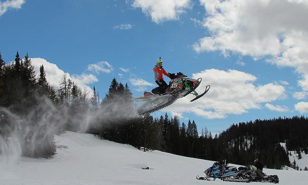 A plume of snowy powder trails behind a snowmobiler in the air.
