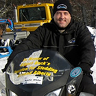 A man in black sitting on a yellow snowmobile.