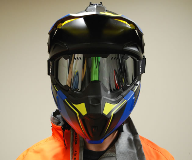A sledder wearing the blue and yellow CKX Titan snowmobile helmet.
