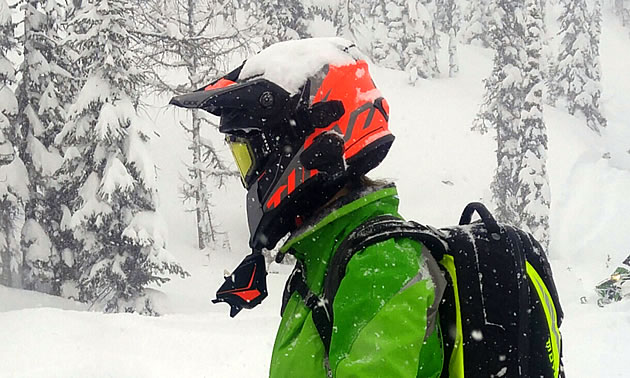 A snowmobiler wearing the orange and black CKX Titan snowmobile helmet in the mountains.