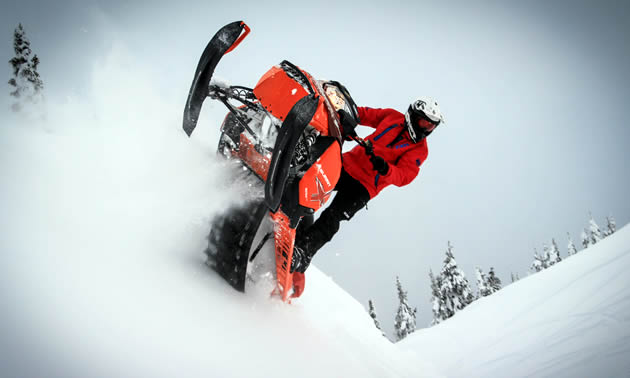 A rider on an orange Ski-Doo sidehilling.