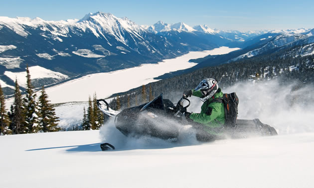 Photo of a guy riding a snowmobile fast across the snow on a ridge overlooking a large valley with mountains on either side.
