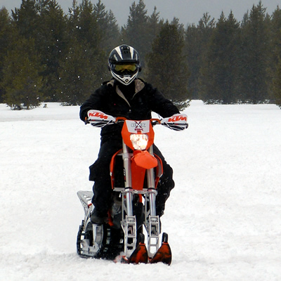 A man riding a CMX snow bike kit on a 500 KTM.