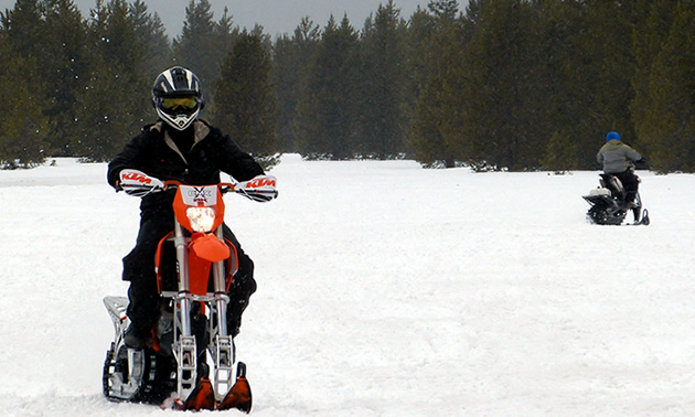 A man in black on a snow bike.