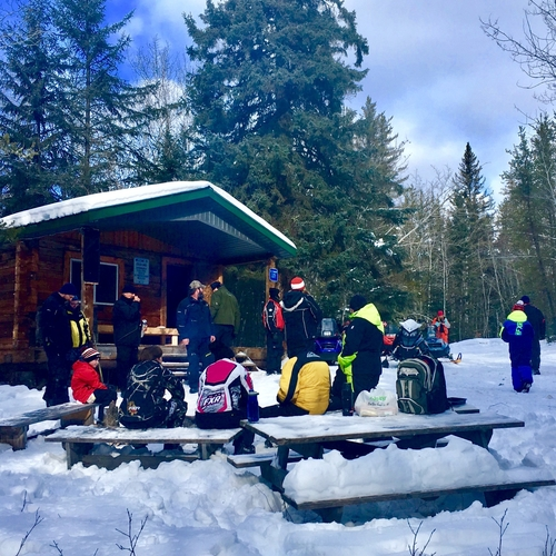 sledders in the distance on a snowy plain