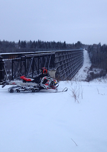 A snowmobile parked in front of the Burnt Beaver river trestle bridge on the Iron Horse Trail, Cold Lake, AB.