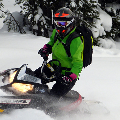 Woman wearing Contessa Jacket on a black sled.