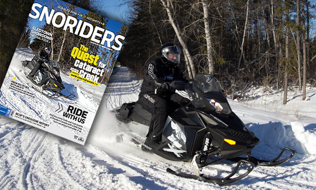 A snowmobiler on a black sled going around a corner on a trail.