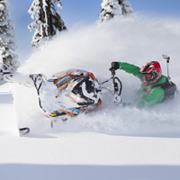 Geoff Kyle in a green snowmobile suit on a Ski-Doo.