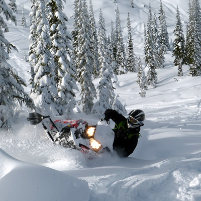 Snowmobiler carving fresh powder around Cranbrook.