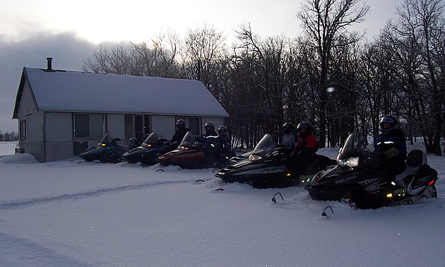 people on sleds near a cabin