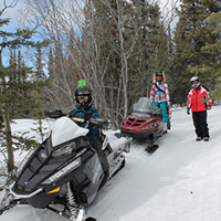 A father and his family riding snowmobiles on a trail.