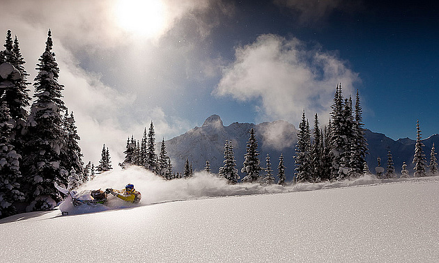 person snowmobiling in powdery snow