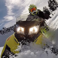 A GoPro photo looking back at a yellow Summit T3 sled and Dave Norona.