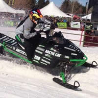 A guy spinning the track on a red and green snowmobile.