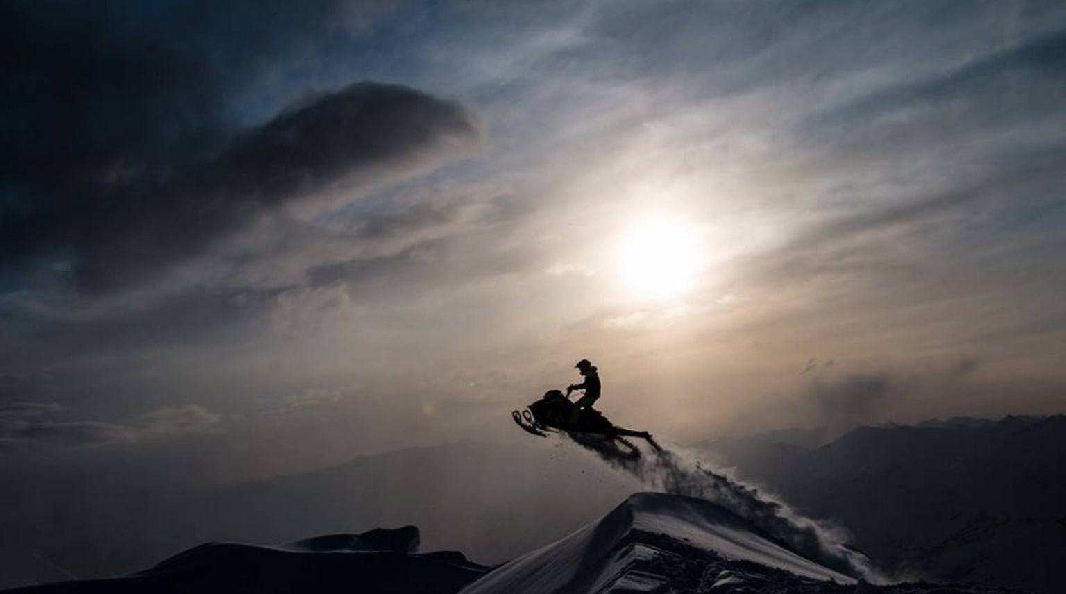 A snowmobiler jumping with the sunset in the background.