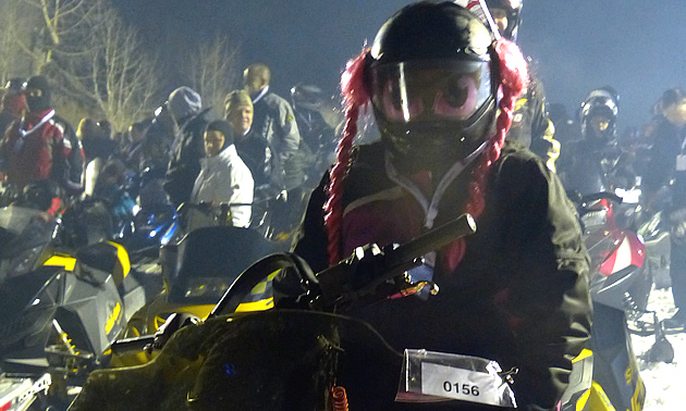 A woman with pink pigtails hanging from her snowmobile helmet.