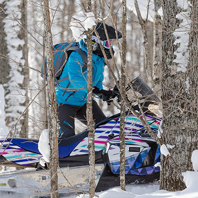 Picture of woman riding a snowmobile through the woods.