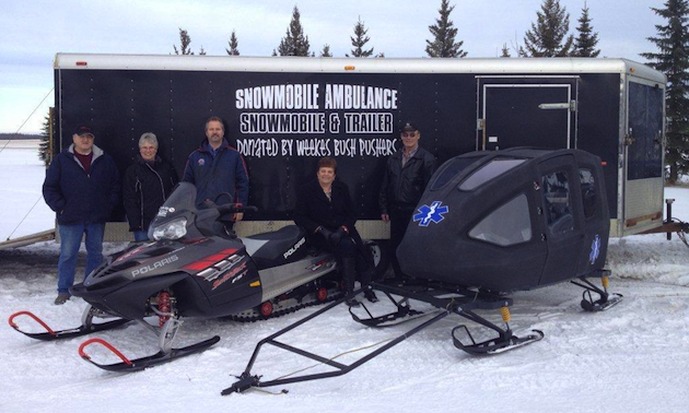 People standing near two snowmobiles and a large trailer