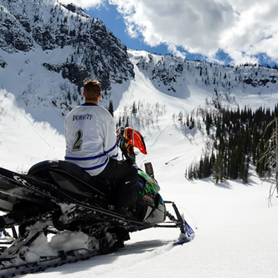 Chris Doratty on his sled looking up at a chute.