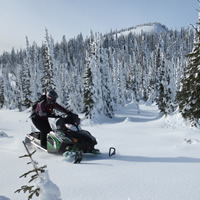 A woman on a snowmobile.