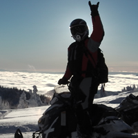 A silhouette of a woman standing on a snowmobile above the clouds.