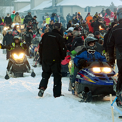 A large group of snowmobilers waiting for a ride to begin.