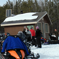Sledders gathered outside of a cabin.