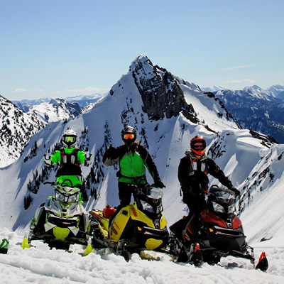 Four sledders parked on top of a mountain with the Rockies in the background.