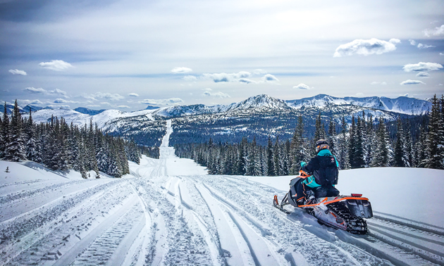 A snowmobiler on the pipeline overlooking Fernie snowmobiling terrain.