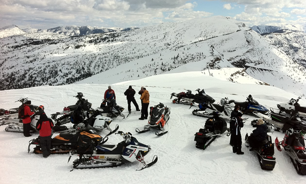 A group of snowmobilers on top of a mountain.