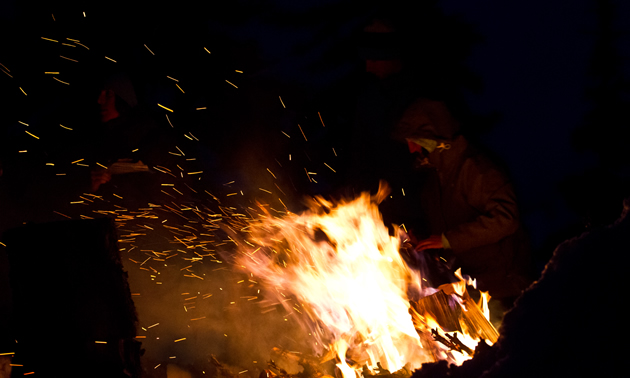 A person siting around a blazing fire.