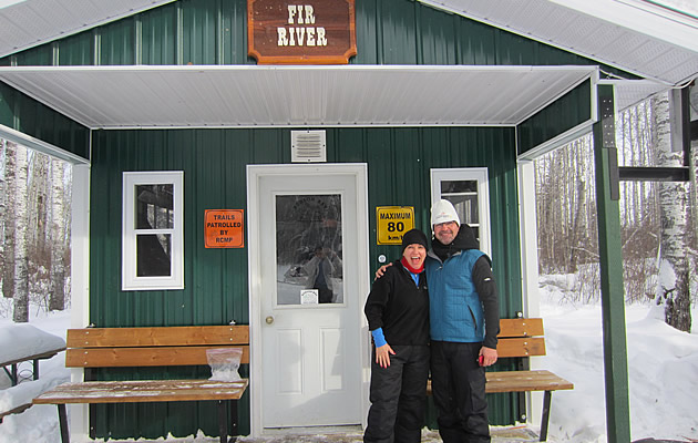 A man and a woman standing on the front step of a snowmobile cabin.