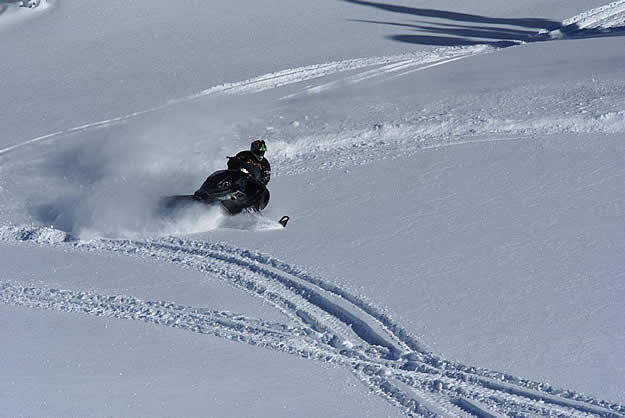 Photo of a snowmobiler carving up snow