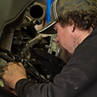 A brown haired man in a ball cap working on an engine.
