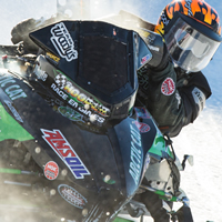 A close up action shot of Gary Moyle on his vintage ice racer snowmobile.
