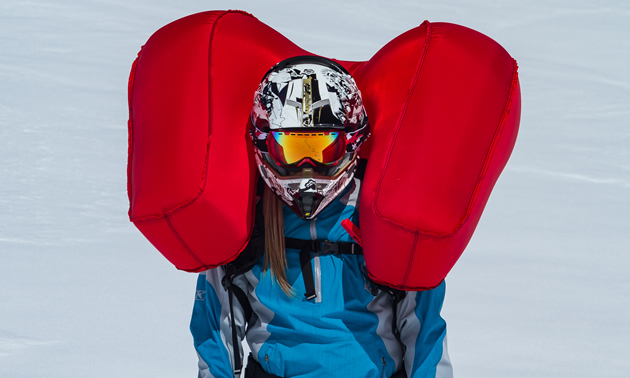 A woman snowmobiler with an airbag inflated.